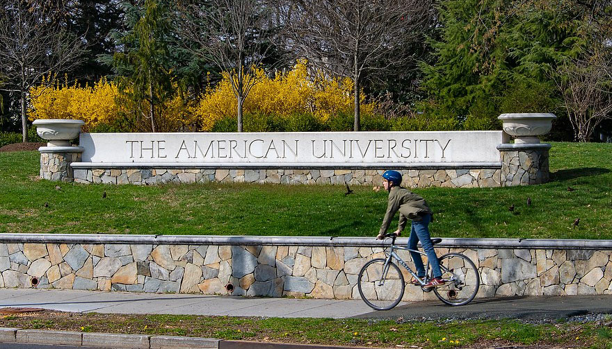 Student rides bike in front of Glover Gate