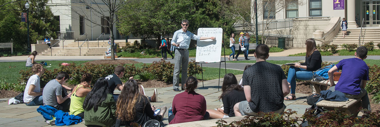A professor conducts a class discussion outside on the quad on a beautiful sunny day.