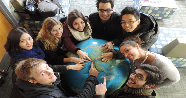 Group of students pointing to DC on a Globe