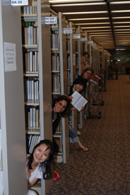 Students peaking out from behind library stacks.