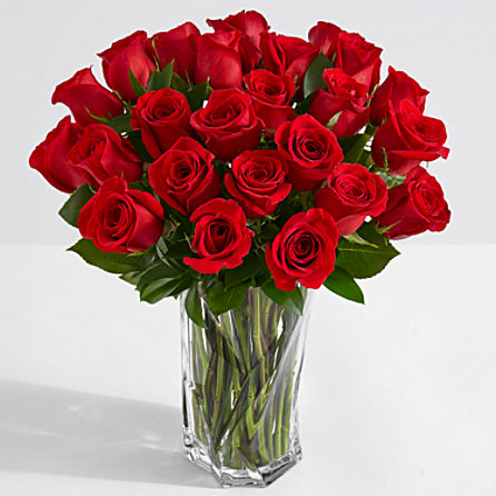 Two dozen red roses in a glass vase