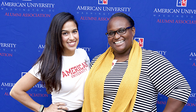 Two alumni volunteers in front of step and repeat banner