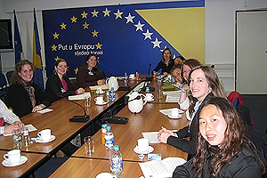 AU Brussels students sit around a conference table with guest speakers