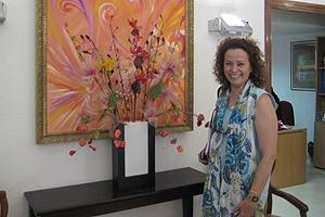 Dr. Maria del Carmen Caballero stands in front of an abstract painting.