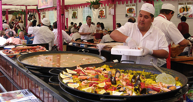 A chef cooks paella in huge pans at a market.