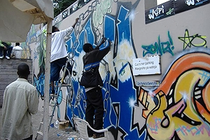 Men spray painting artistic graffiti on city walls.