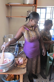 Kenyan woman cooking with a bio-gas heated stove.