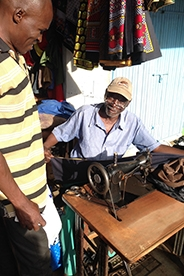Kenyan man sewing.