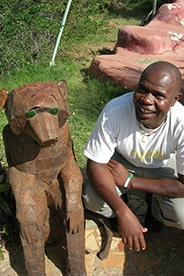 AU Nairobi program assistant standing with a statue.
