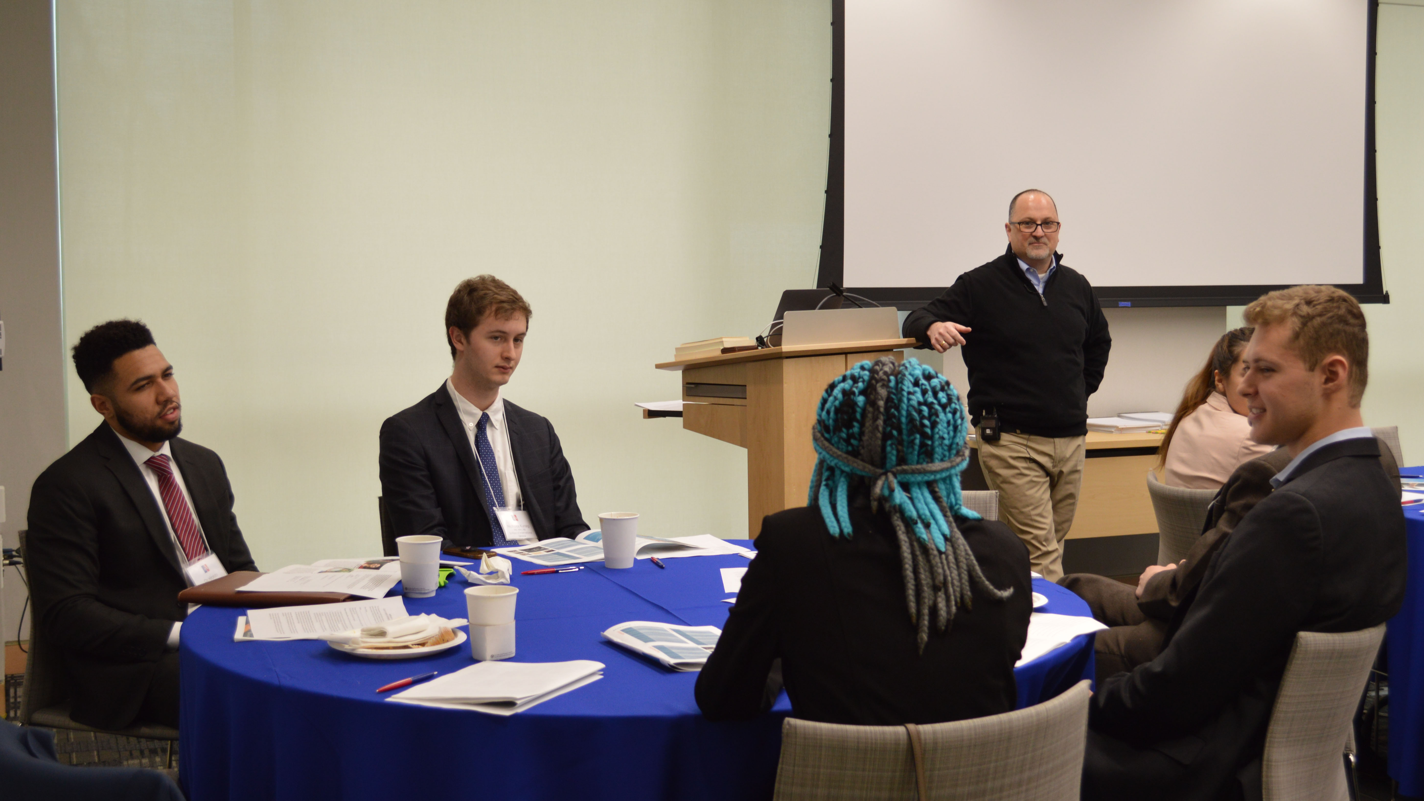 An employer speaks to students seated at a round table