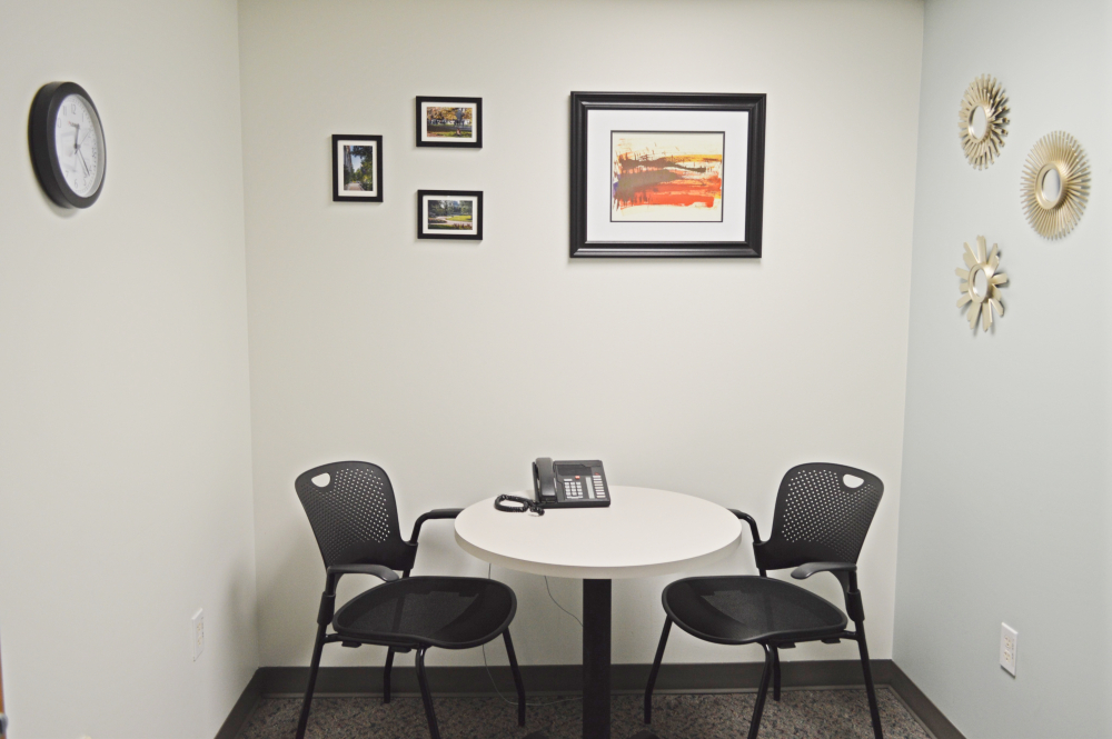 Interview room with small table, two chairs, phone, and paintings on the walls