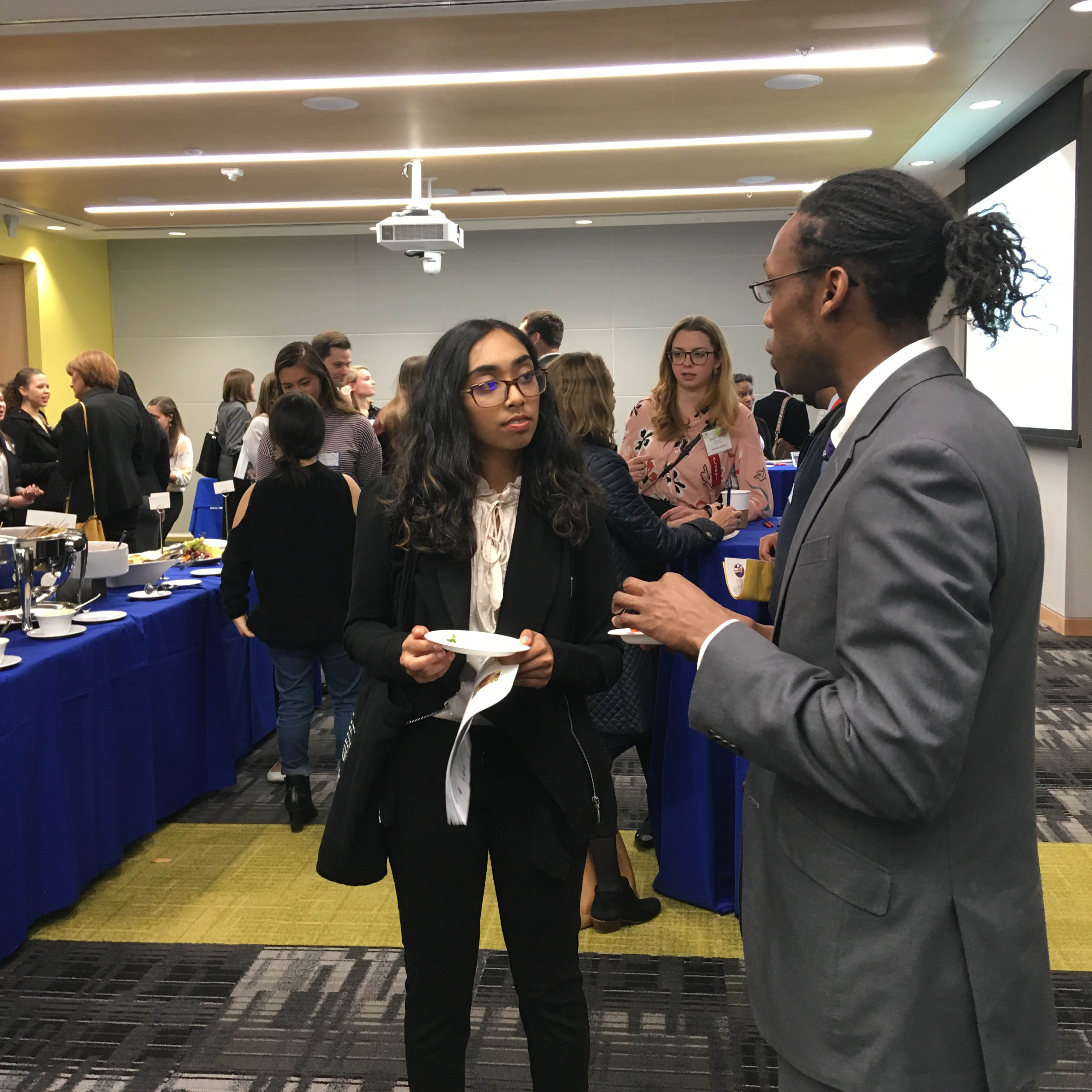 A student talks to a professor at the public health networking reception in Constitution Hall, East Campus