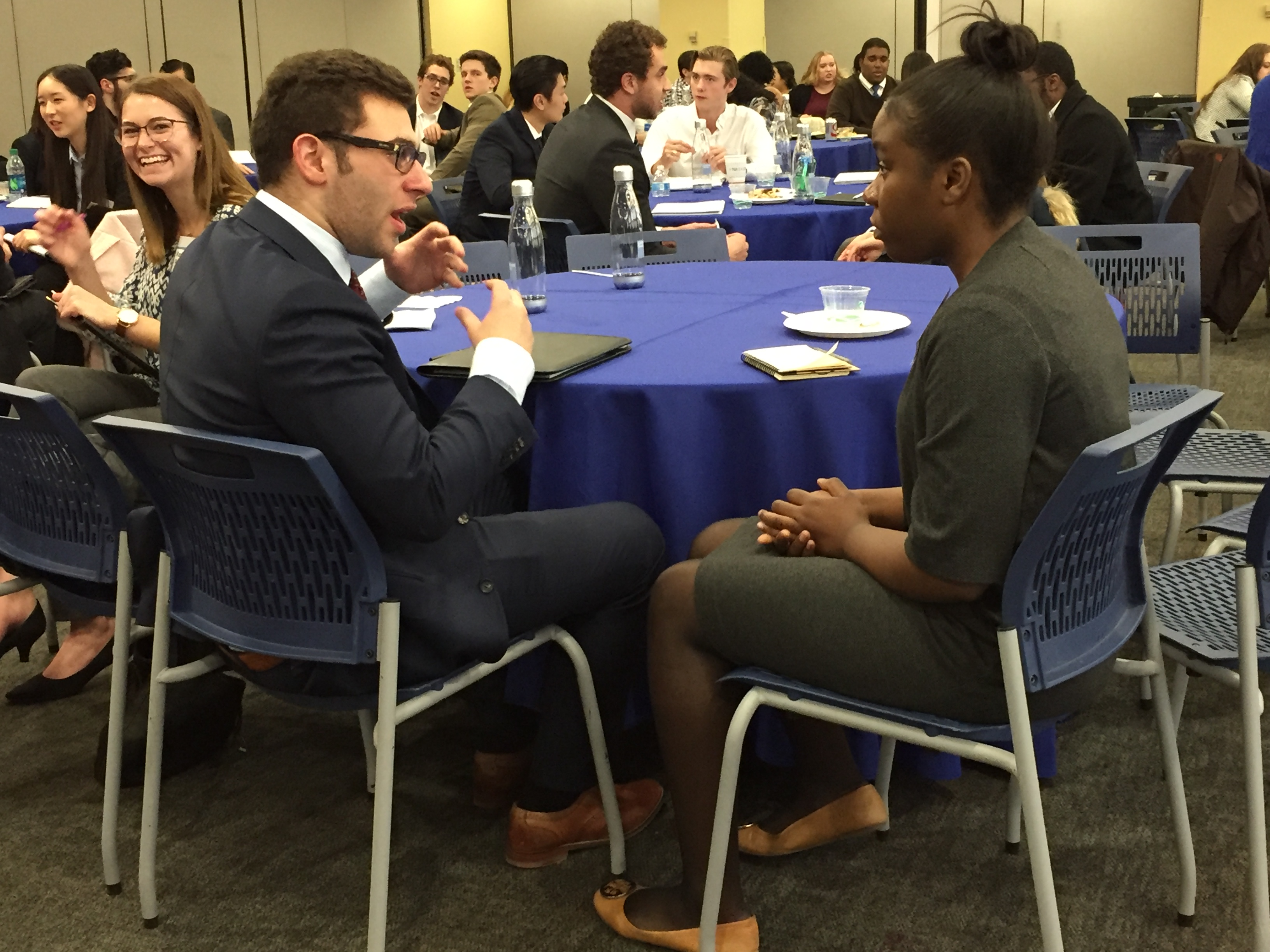 Two students talk at a round table. The male student wears a blue suit and glasses and speaks to the female student wearing a gray cardigan and skirt