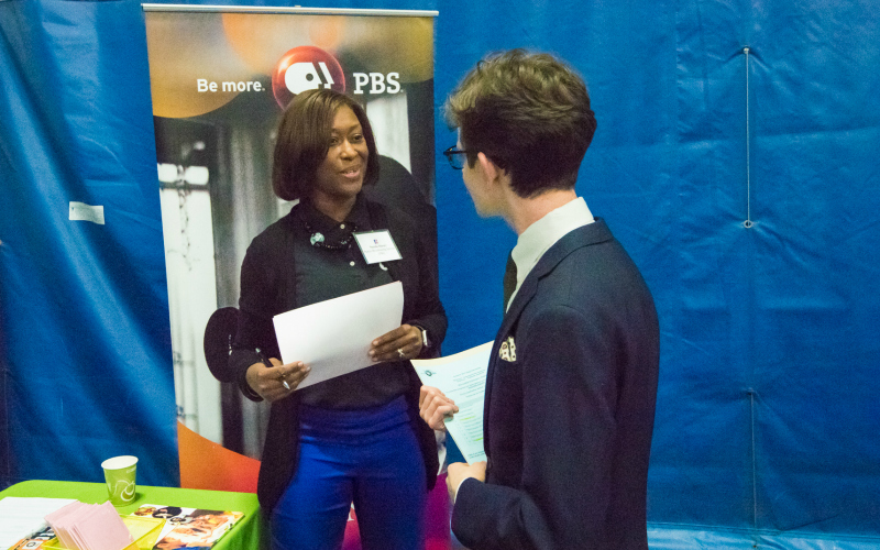 A PBS recruiter shakes hands with a student at the fair