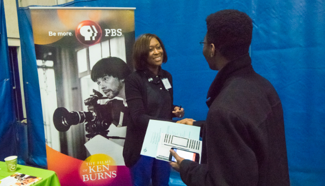 A PBS representative shakes hands with an AU student at the Job & Internship Fair