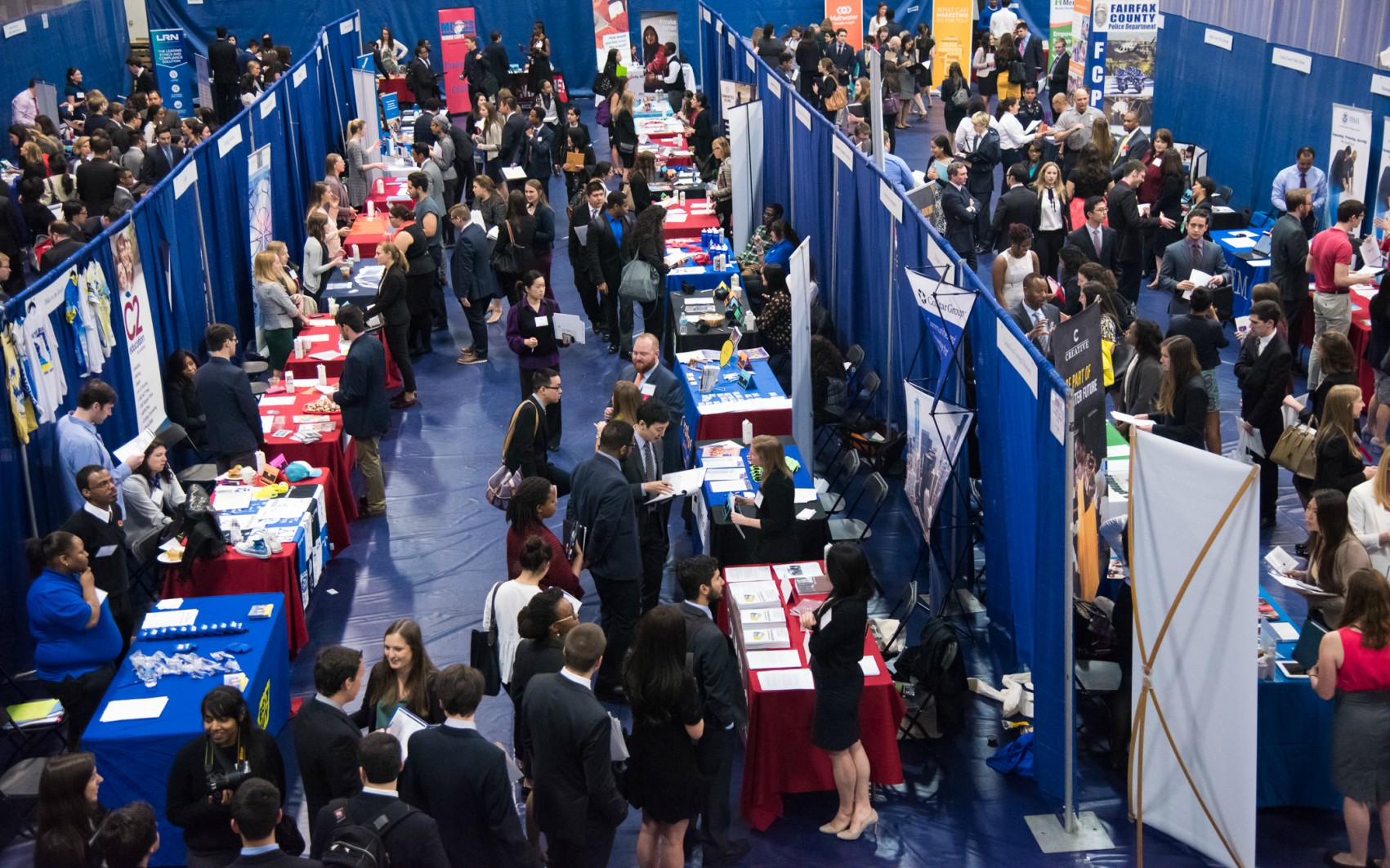 looking down on rows of employer booths at the job fair; blue backdrop with many students