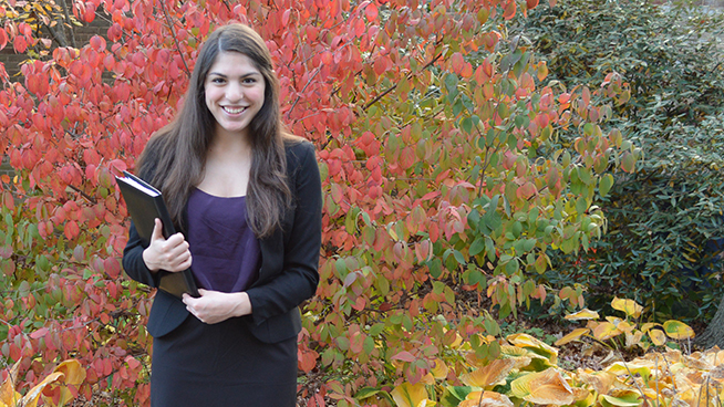 young woman dressed in black skirt suit and purple blouse standing in front of autumn leaves