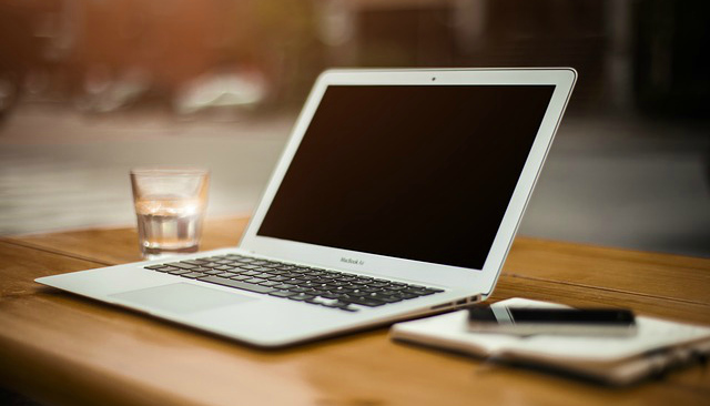 A laptop and writing pad on a desk