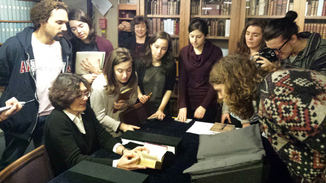 A group of students lean in close to listen to a bespectacled curator.