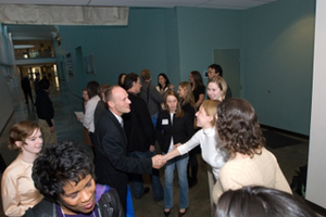 People shake hands at a gallery event