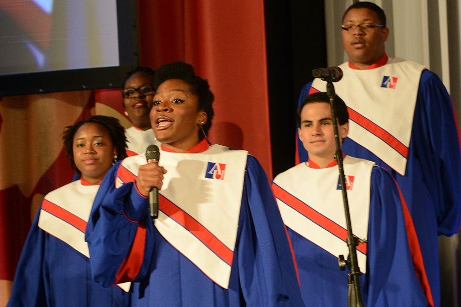 A woman in choir robes sings into a microphone with four choir members behind her