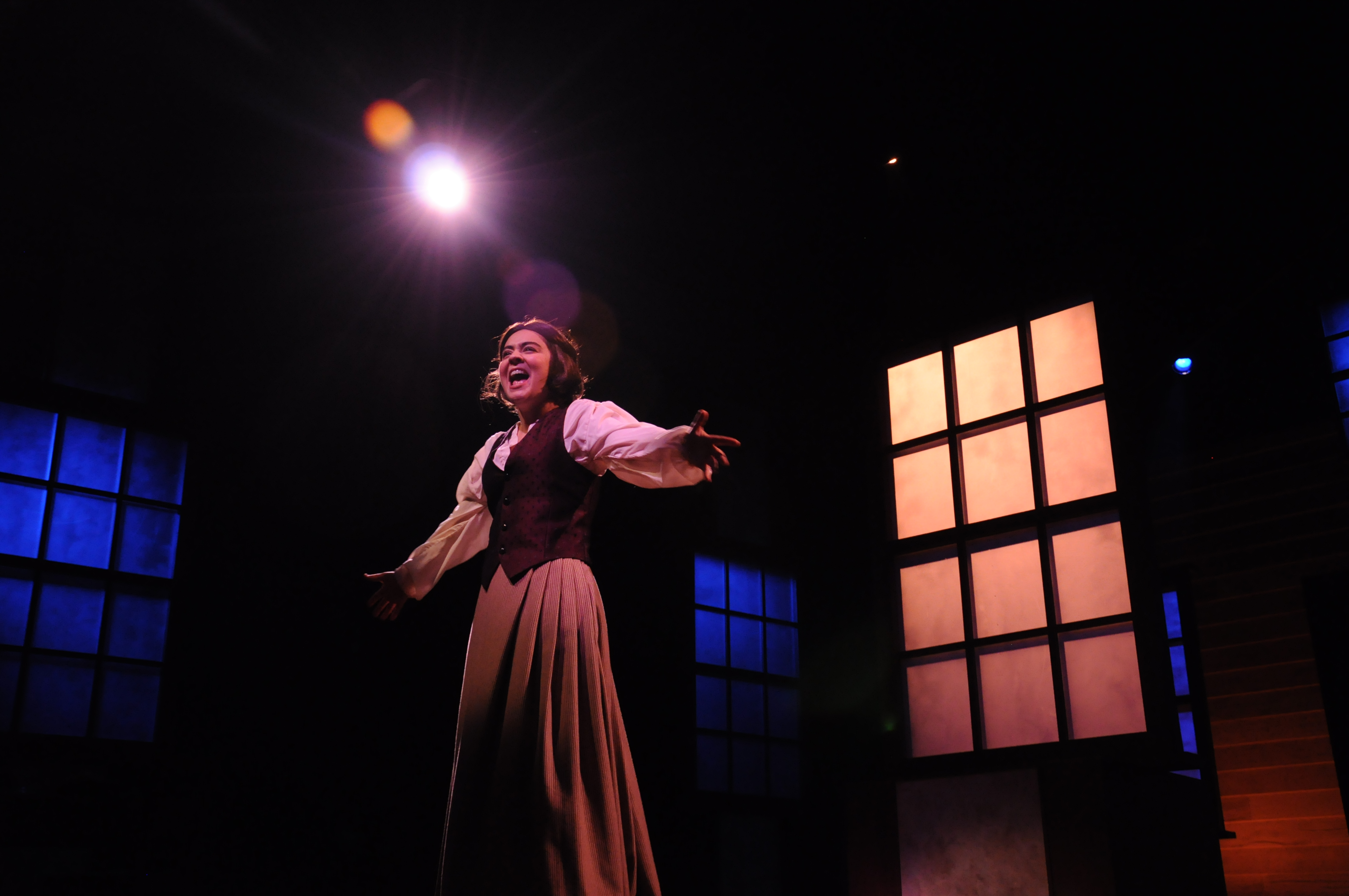 An actor in American University's 2017 production of Little Women sings on stage at the Greenberg Theatre.