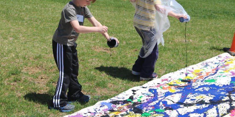 Children on a lawn dribbling paint onto paper