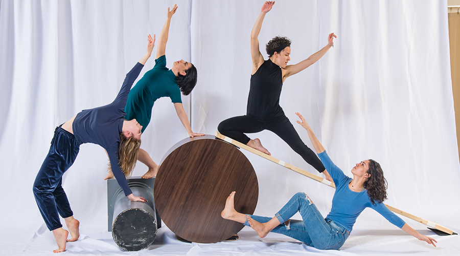 Four people pose atop tables and boards