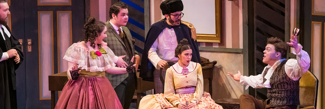 Onstage, four people listen to a seated man tell an animated story. All are in mid-1800s clothing