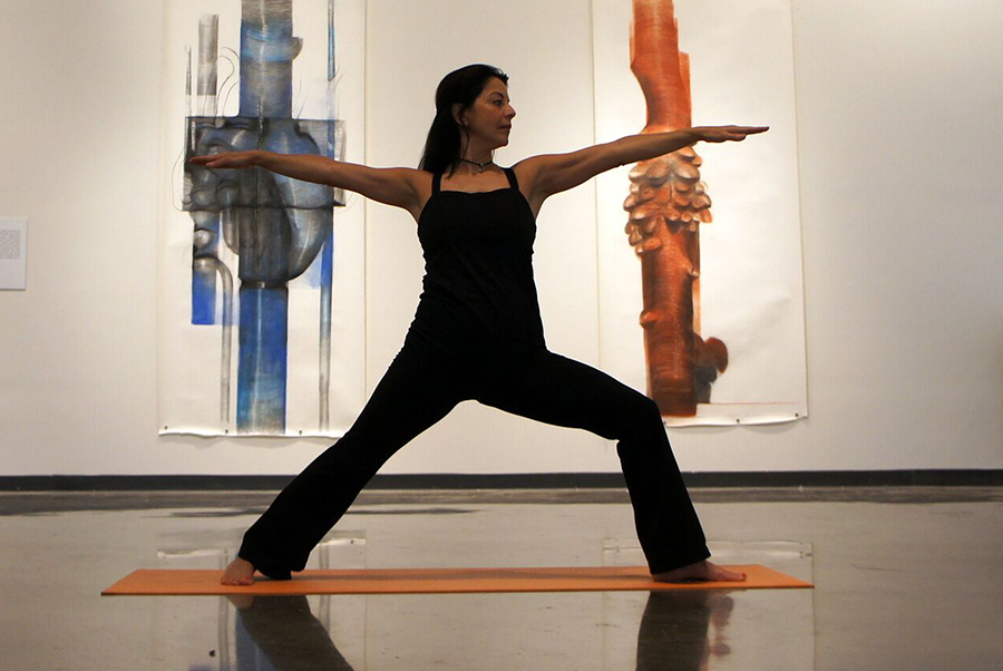 A woman in warrior pose on a yoga mat in front of two brightly-colored paintings