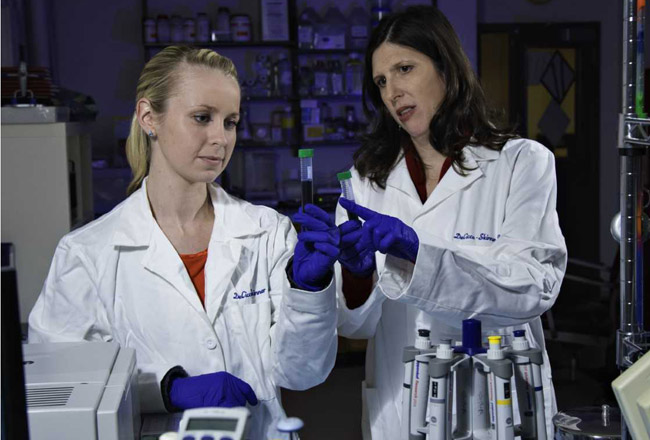 Two scientists in lab coats examine a test tube