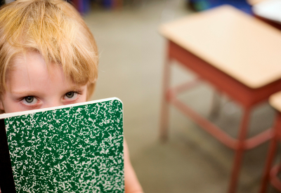 A child hides behind a composition book.