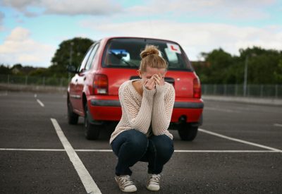 A young girl crys behind a car in a parking lot.