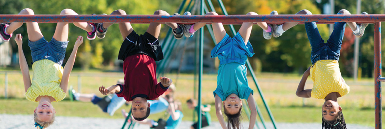 Kids hanging upside down on playground.