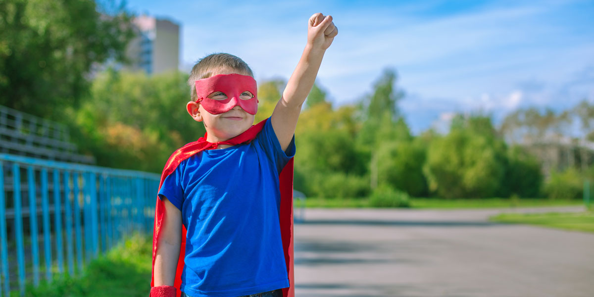 Kid dressed as a superhero raises one fist to the sky