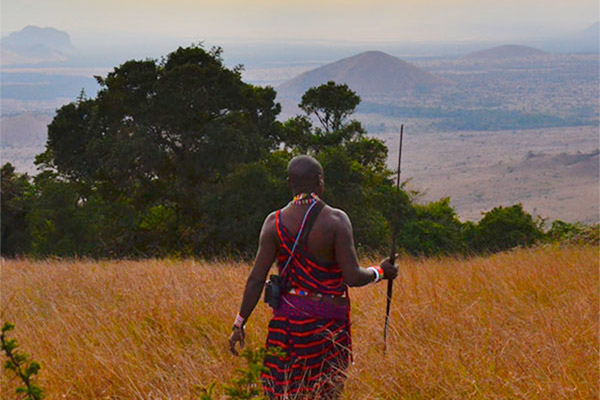 Person in native garb walking in Kenyan grassland and holding spear.