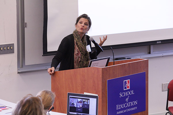 A woman speaks at a podium in front of the School of Education