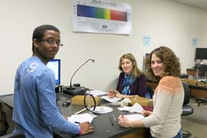 Three students work at a lab table