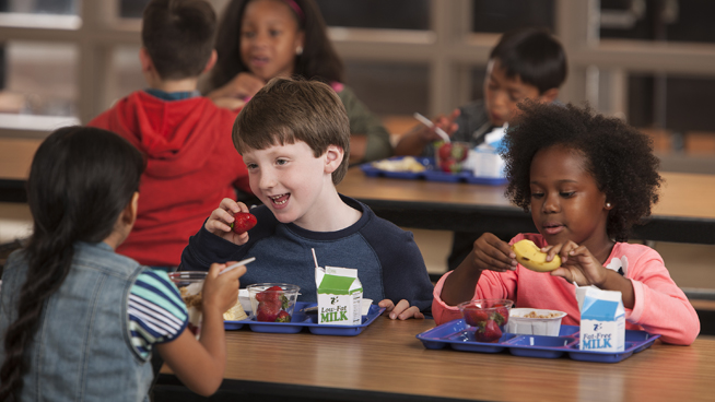 Children at long tables eat a school lunch