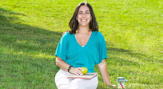 Person sitting on grass with books on lap