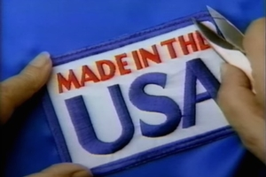"A red, white, and blue patch that reads ""Made in the USA"" is attached to a piece of blue fabric."