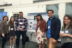 NPR Practicum Group members standing with their poster