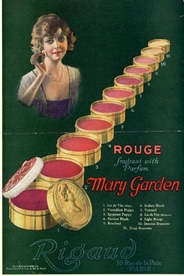 An old magazine advertisement for Mary Garden rouge. A young woman applying rouge, along with several tins of different colored rouges.