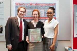 "Three people hold the ""Who's a Washingtonian?"" program outline binder"