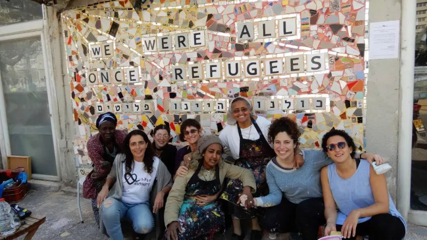 "Women posed before ""we were all once refugee"" wall."