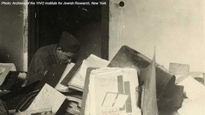 Archival photo: a man digs through rubble