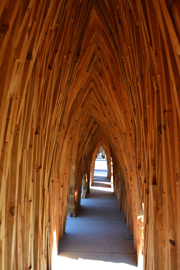 A view down the center of a narrow tunnel, big enough to walk through, whose sides are composed of long planks of wood that curve inward, giving the tunnel a pointed roof. There are a few doorways to the sides, too low to escape through except by crawling
