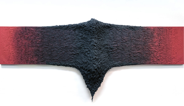 Two ends of a long boardlike work start red and get black at the center. The black middle is raised and textured like fur, meeting in a peak that drips off the board.