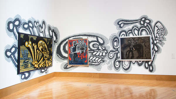 Three of Luna's paintings as installed overtop images of skeletons and bones applied directly to the gallery wall