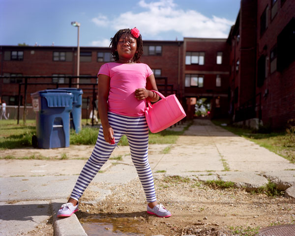 Photo of a young girl in a bright pink shirt and striped leggings standing in the sunshine astride a curb in front of some recycling bins and a brick building. She holds a pink purse and a pair of red scissors.